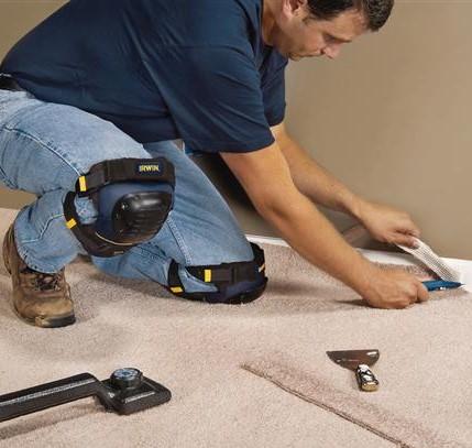 Tradesman installing carpet underlay